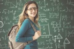 Estudiante con la mochila en fondo de la pizarra Imágenes de archivo libres de regalías