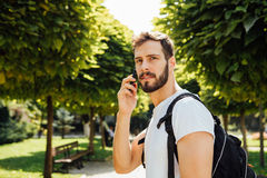 Estudiante con la mochila que habla en el teléfono móvil Foto de archivo libre de regalías