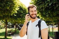 Estudiante con la mochila que habla en el teléfono móvil Imágenes de archivo libres de regalías