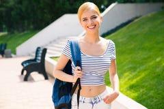 Estudiante con la mochila que se coloca al aire libre Fotos de archivo