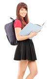 Estudiante con la mochila que sostiene un libro Fotos de archivo