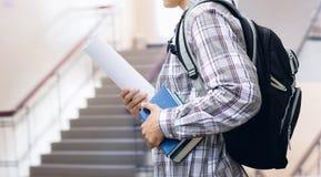 Estudiante con la mochila y los libros en el fondo de la escalera Foto de archivo
