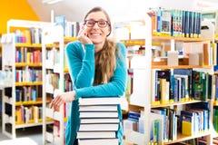 Estudiante con la pila de aprendizaje de libros en biblioteca Foto de archivo