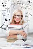Estudiante con la pila de libros y de garabatos Foto de archivo libre de regalías