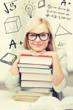 Estudiante con la pila de libros y de garabatos Imagen de archivo