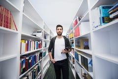 Estudiante con la tableta en biblioteca Imagenes de archivo