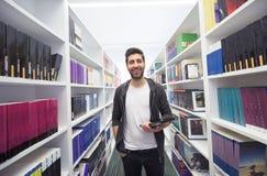 Estudiante con la tableta en biblioteca Foto de archivo libre de regalías