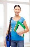 Estudiante con las carpetas, PC de la tableta y el bolso en la escuela Fotos de archivo libres de regalías