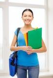 Estudiante con las carpetas y bolso en la escuela Imágenes de archivo libres de regalías