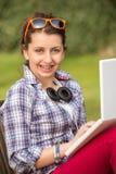 Estudiante con los apoyos usando el ordenador portátil en el parque Foto de archivo
