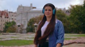 Estudiante con los auriculares al aire libre almacen de metraje de vídeo