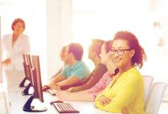 Estudiante con los compañeros de clase en clase del ordenador Imagen de archivo libre de regalías