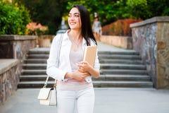 Estudiante con los cuadernos y bolso delante de la universidad de la universidad imagen de archivo libre de regalías