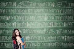 Estudiante con los libros en la pizarra Imágenes de archivo libres de regalías