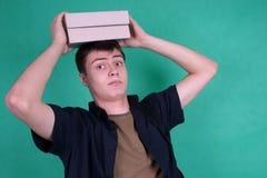 Estudiante con los libros pesados en su cabeza Foto de archivo