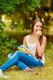 Estudiante con los libros que come una manzana Foto de archivo