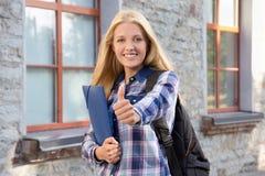 Estudiante con los pulgares de la mochila para arriba Imagen de archivo libre de regalías