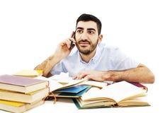Estudiante con los teléfonos móviles en el escritorio de la escuela Imagen de archivo libre de regalías
