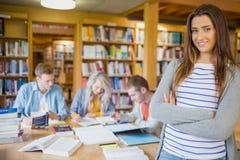 Estudiante con otros en fondo en la biblioteca Fotos de archivo libres de regalías