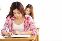 Estudiante con otros notas de la escritura en la sala de clase Foto de archivo libre de regalías