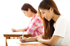 Estudiante con otros notas de la escritura en la sala de clase Fotos de archivo