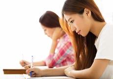 Estudiante con otros notas de la escritura en la sala de clase Imagen de archivo libre de regalías