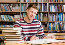 Estudiante con PC de la tableta en la biblioteca Foto de archivo libre de regalías