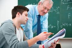 Estudiante con un profesor en sala de clase Fotografía de archivo
