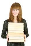 Estudiante con una pila de libros Imagen de archivo libre de regalías