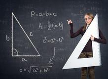 Estudiante con una regla grande y teorema pitagórico en la pizarra Fotografía de archivo libre de regalías
