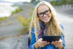 Estudiante con una tableta al aire libre en verano Foto de archivo libre de regalías
