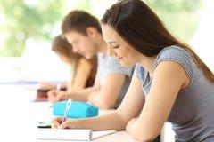 Estudiante concentrado que toma notas en una sala de clase Foto de archivo