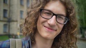 Estudiante confiado hermoso que toca sus vidrios y que sonríe en la cámara, colocándose en la calle cerca de la universidad, aleg metrajes