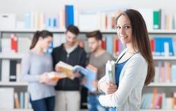 Estudiante confiado que presenta en la biblioteca Fotografía de archivo