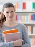 Estudiante confiado que presenta en la biblioteca Imagenes de archivo