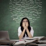 Estudiante confuso que estudia para el examen Imagen de archivo libre de regalías