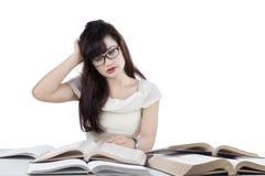 Estudiante confuso que lee muchos libros 2 Foto de archivo libre de regalías