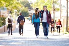 Estudiante Couple Walking Outdoors en campus universitario Fotos de archivo libres de regalías