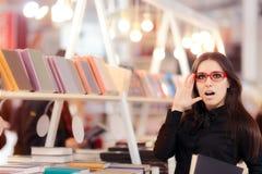 Estudiante curioso Girl Thinking qué libros a comprar Fotos de archivo