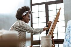 Estudiante de arte internacional de emisi?n que se sienta cerca de ventana y de la pintura imagen de archivo libre de regalías
