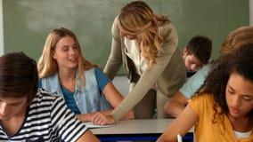 Estudiante de ayuda del profesor con el papel metrajes