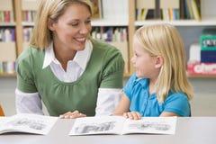 Estudiante de ayuda del profesor con habilidades de lectura foto de archivo libre de regalías