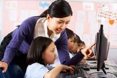 Estudiante de ayuda del profesor durante clase del ordenador Fotografía de archivo