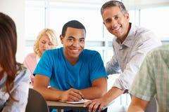 Estudiante de ayuda del profesor particular durante clase Imagen de archivo libre de regalías