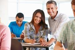 Estudiante de ayuda del profesor particular en clase Imagen de archivo
