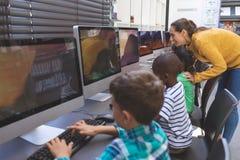 Estudiante de enseñanza del profesor en sala de ordenadores fotos de archivo