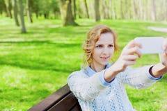Estudiante de la chica joven que se divierte y que toma la foto del selfie en la cámara del smartphone al aire libre en parque ve Imágenes de archivo libres de regalías