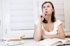 Estudiante de la chica joven que se prepara para el examen con los libros la mujer está estudiando con los libros de texto Prepar Imagenes de archivo