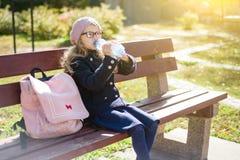 Estudiante de la escuela primaria de la niña que se sienta en banco con la mochila, agua potable de la botella Imagen de archivo
