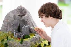 Estudiante de la escuela que trabaja en proyecto de edificio modelo Imagen de archivo libre de regalías
